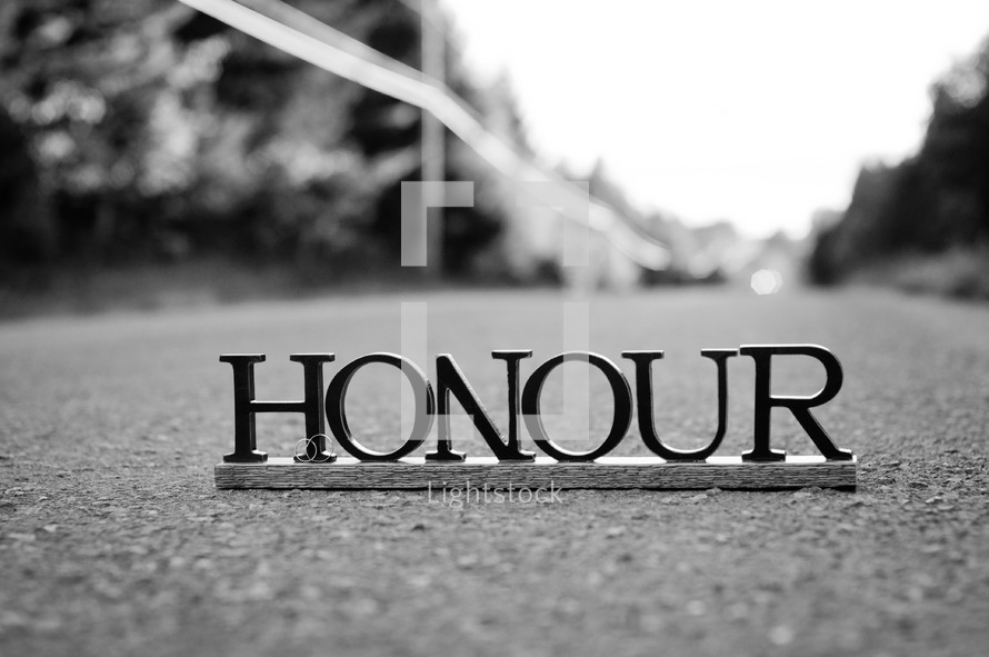 """Letters spelling """"honour"""" on the pavement."""