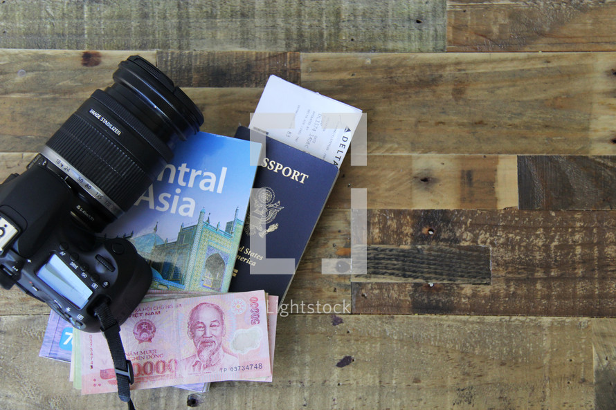 travel, camera, passport, map, book on Central Asia, money, and boarding passes  on a wood floor