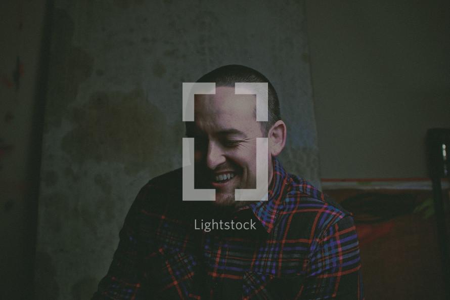 a man in a plaid shirt laughing