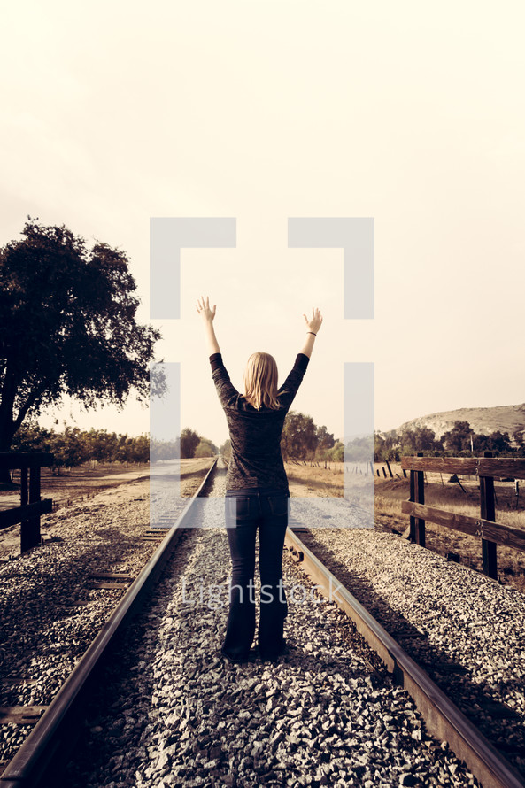 woman with arms raised on railroad tracks