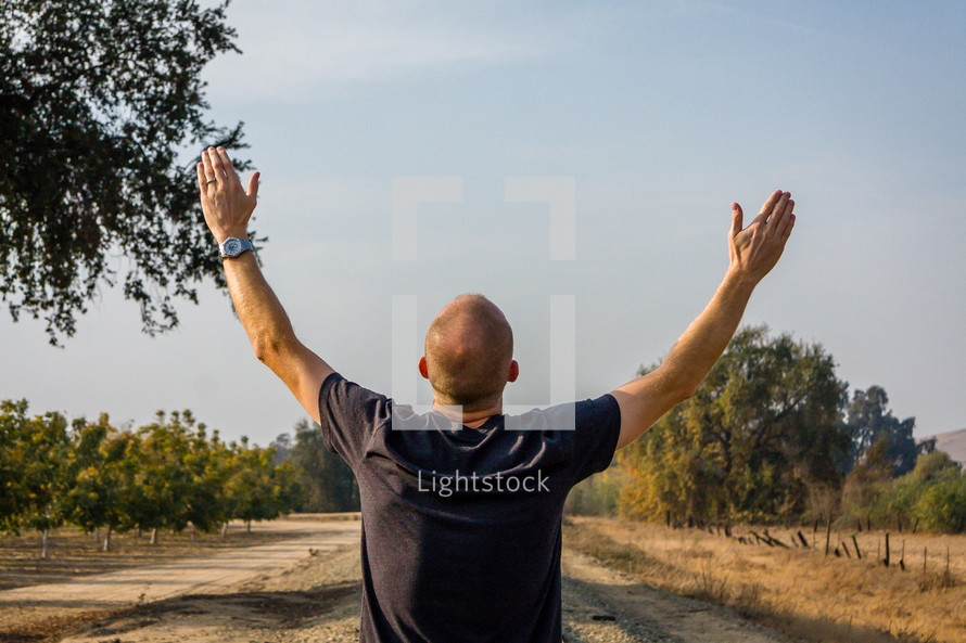 man with arms raised in worship standing on railroad tracks