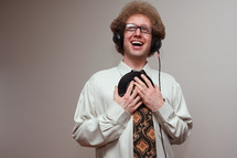 A laughing man in headphones holding a vinyl record to his chest.