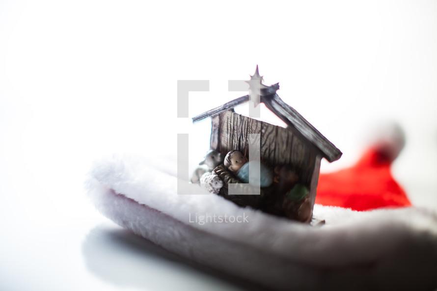 manger ornament on a Santa hat