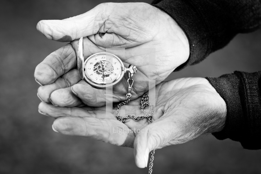 Elderly hands holding a pocket watch.