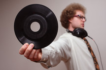 A man wearing headphones and holding out a vinyl record.