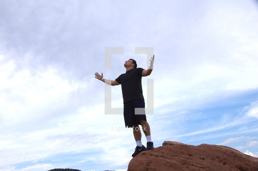 man standing on a red rock with arms raised