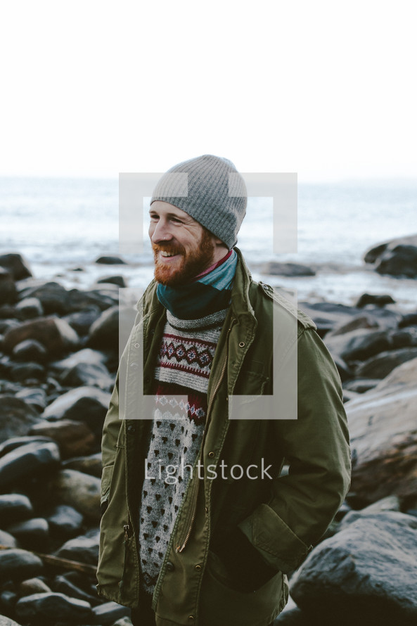 a man in a sweater, jacket, and beanie standing on a rocky shore