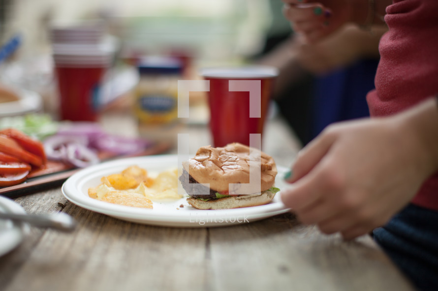eating food at a cookout - hamburger on a plate