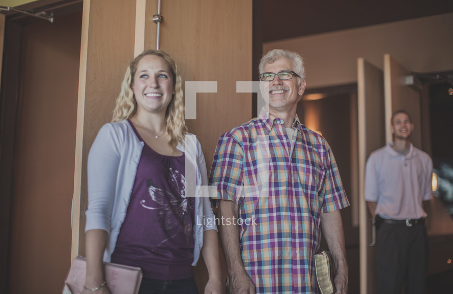 greeters standing at the entrance of a church welcoming others