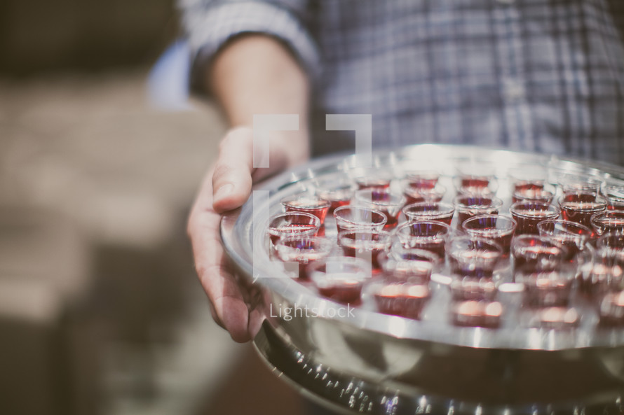 man holding a tray of communion cups