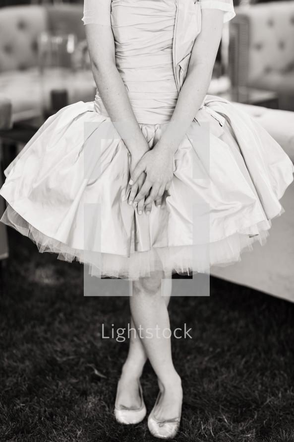torso of a woman in a formal dress feet crossed