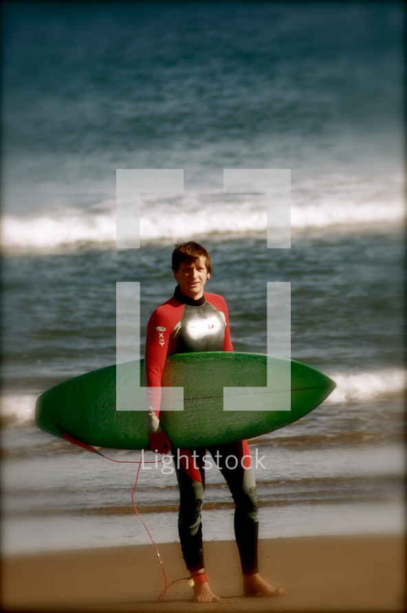 man in a wetsuit on a beach holding a surfboard