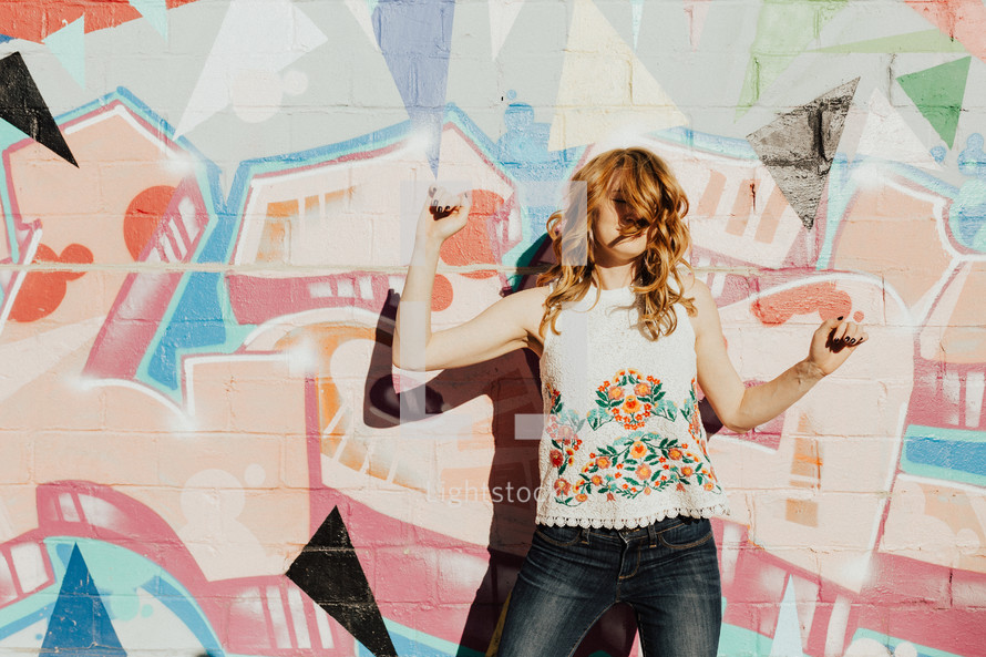a joyous playful woman standing in front of a graffiti covered wall