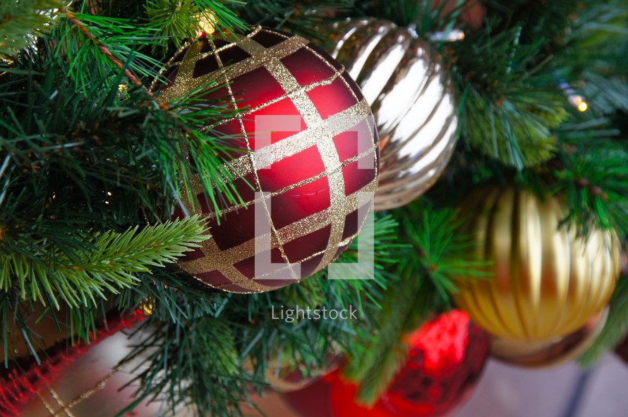 Red and gold ball Christmas ornaments hanging from pine Christmas tree.