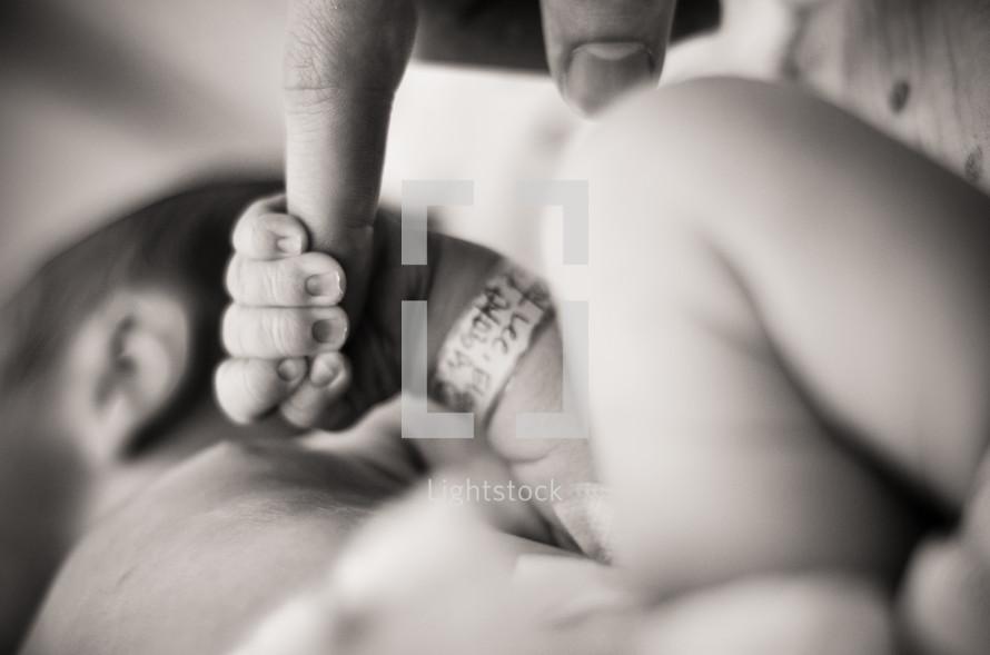 Infant holding father's finger