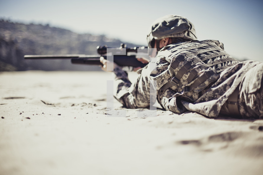 Soldier aiming gun while lying on rock.