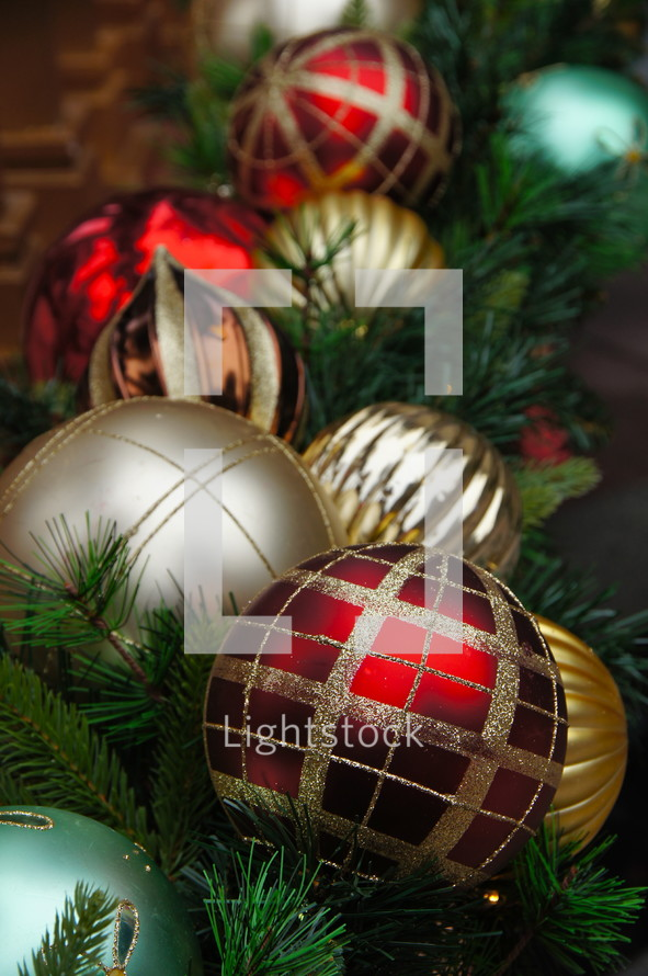 Red and gold Christmas ball ornaments on pine needles.