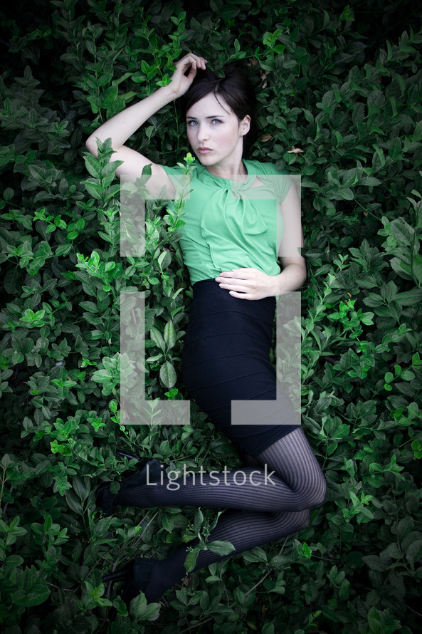 Ophelia; woman in green shirt and black skirt lying on a bed of green plants.