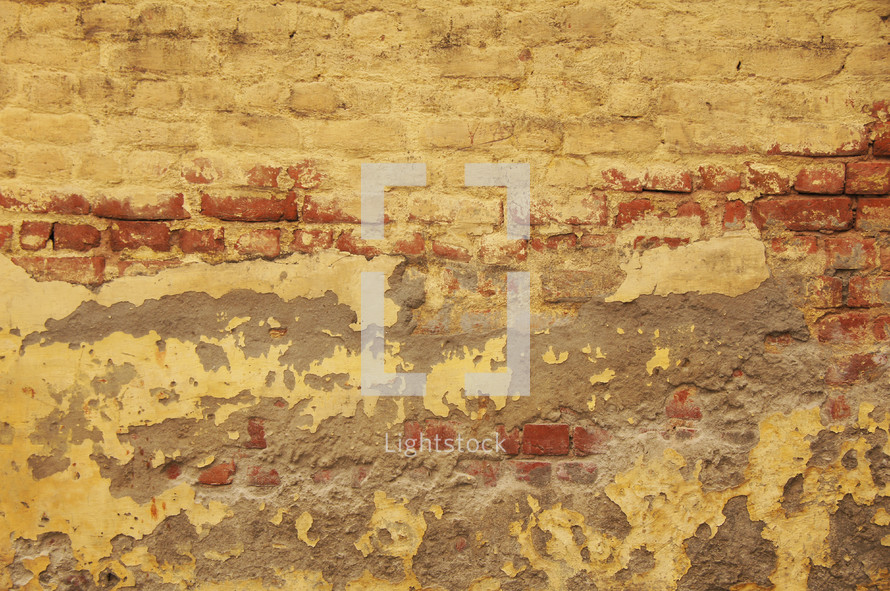 Eroded, plastered, painted brick wall