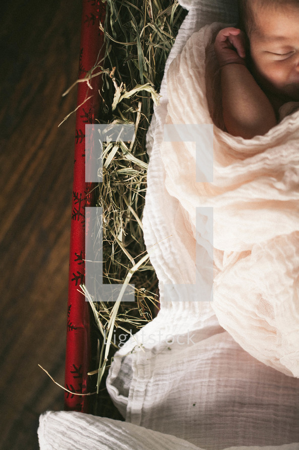 Baby Jesus lying in a Christmas present full of hay