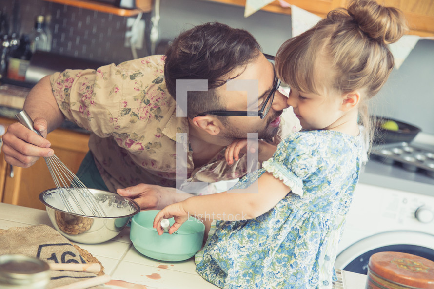 a father and daughter baking together in the kitchen