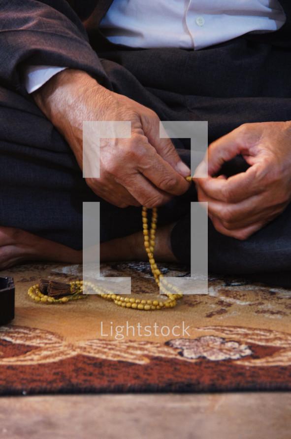 Man praying using prayer beads.