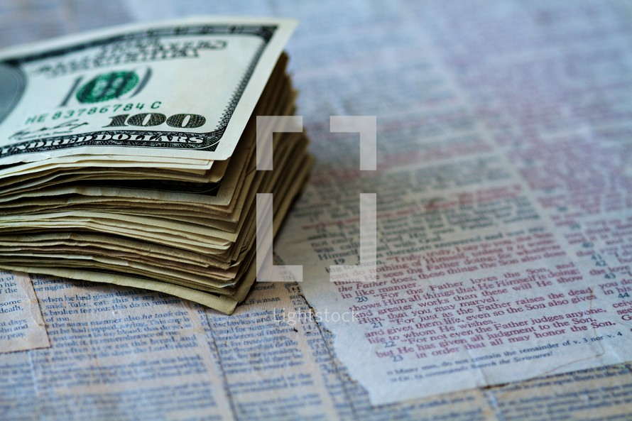 A stack of one hundred dollar bills sits on pages of scripture.