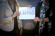 people holding a united sign