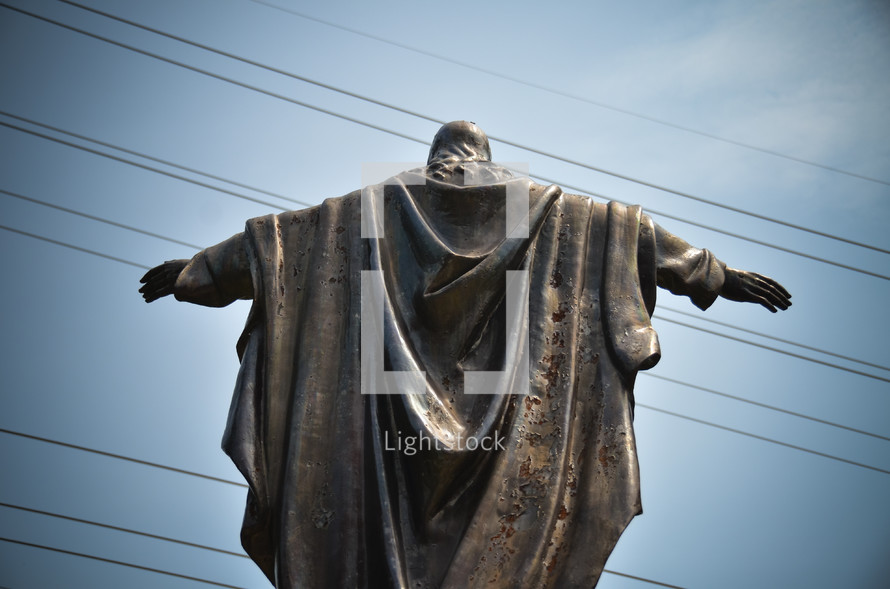 statue of Jesus with his arms outstretched with power lines in the background