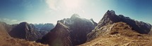 Sun light in sky over a jagged mountain range on a journey seeking adventure.