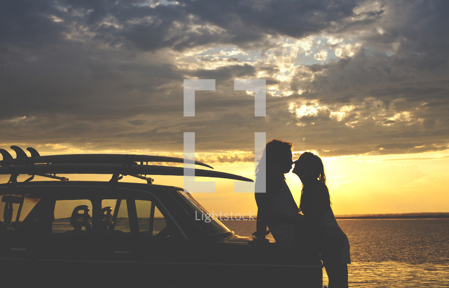 a couple leaning on a car about to kiss at sunset