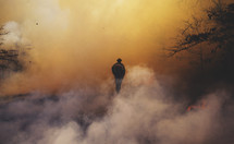 smoke surrounding a fireman as he outs out a forest fire