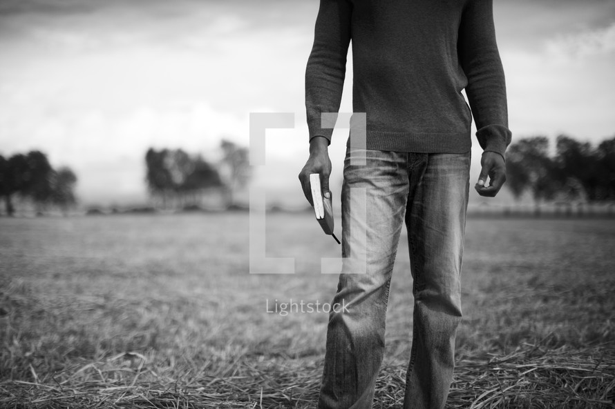 A man holding a Bible stands confidently outside