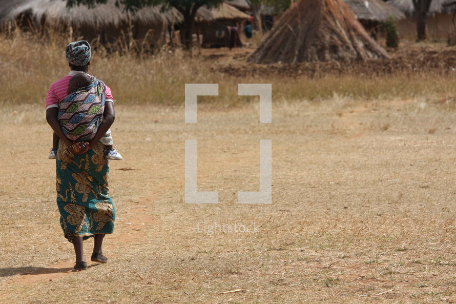 Woman carrying baby through field