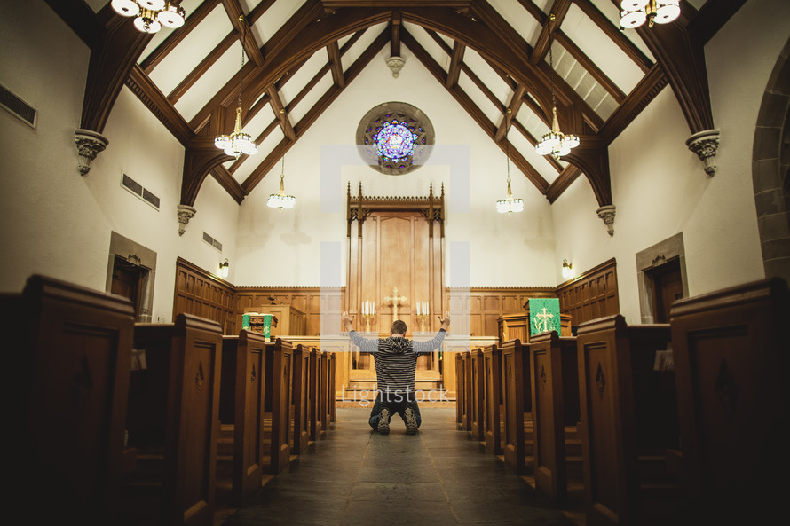 Man kneeling in prayer at church altar