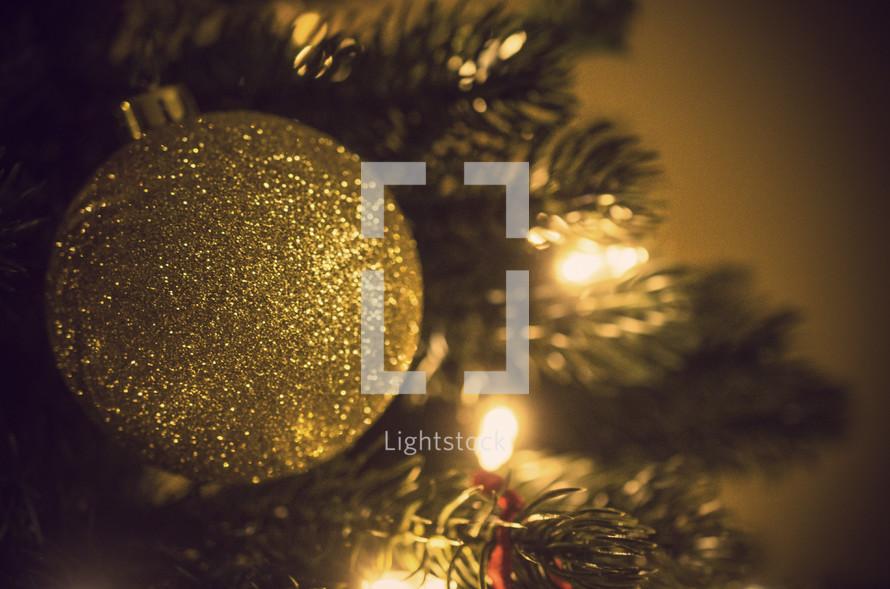 gold glitter ball Christmas ornament on a Christmas tree