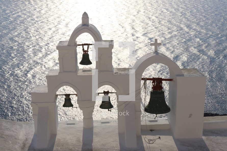 white bell tower with bells over looking the ocean