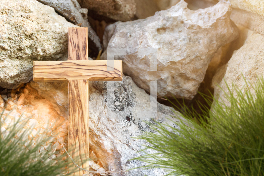wood cross in front of rocks