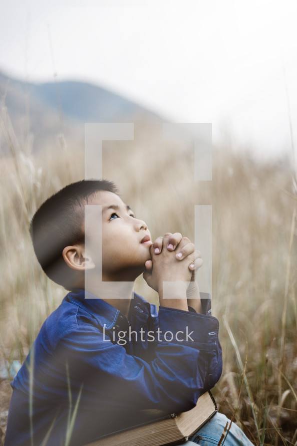 child looking up to God in prayer