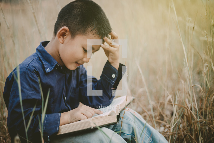 a child reading a Bible outdoors
