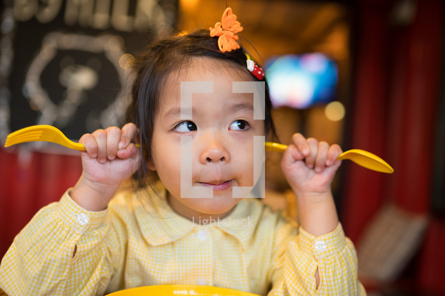 silly Asian child with fork and knife ready to eat in restaurant.