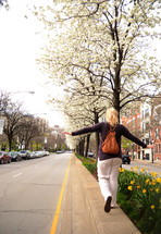 A woman walking along a street, balancing on the curb.