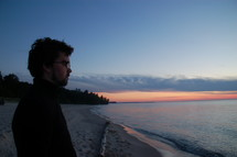 A man looks at a lake at sunset.
