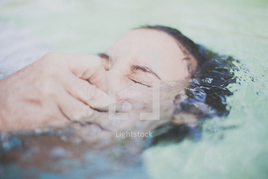 Woman being baptized in a pool of water.