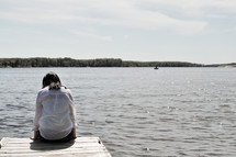 a woman sitting at the end of a dock