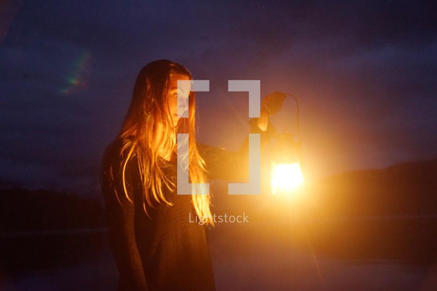 a woman holding a glowing lantern