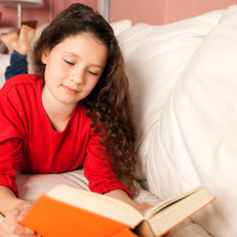 girl child reading a book on her bed