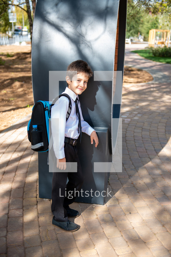 portrait of a boy in dress clothes with a book bag