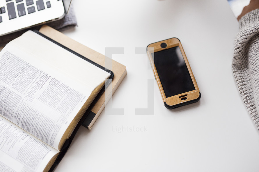 a desk with an open Bible, laptop, cellphone, and journal