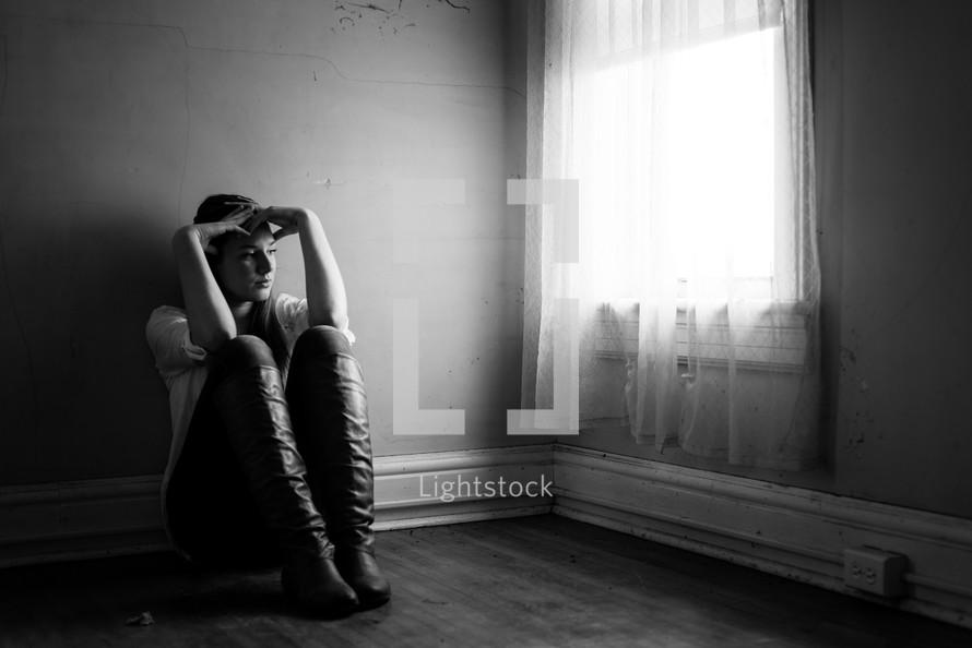 teen girl sitting in an empty room